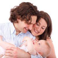 赤ちゃんを抱っこするパパと寄り添うママ