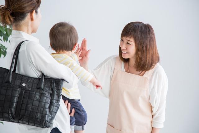 保育士とハイタッチする赤ちゃん