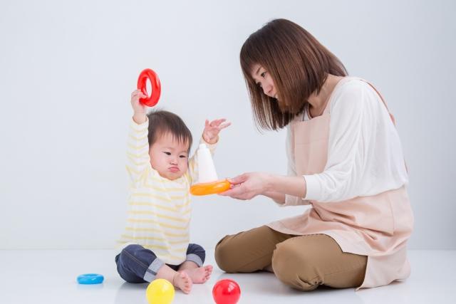 赤ちゃんと輪投げで遊ぶ保育士