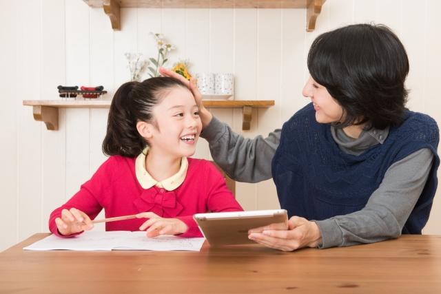 勉強をする女の子と褒める母